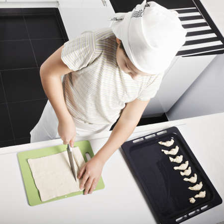 Caucasian boy cutting dough while cooking croissants at the kitchen photo