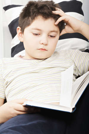 Caucasian boy reading book while laying down on sofa closeup photo