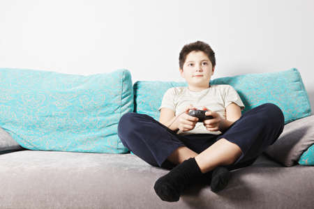 Caucasian kid playing video game while sitting on couch legs crossed photo