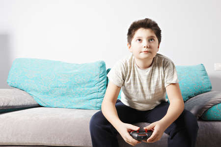 playing video game: Caucasian boy playing video game while sitting on couch
