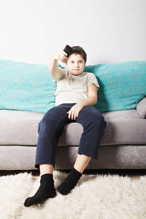 Caucasian boy switching TV channels with remote control while sitting on couch photo