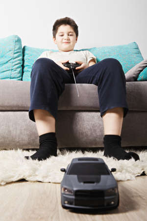Caucasian boy playing radio remote controlled toy car while sitting on the couch photo