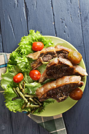 loin chops: Grilled lamb loin chops with pickled tomatoes on lettuce leaves overhead