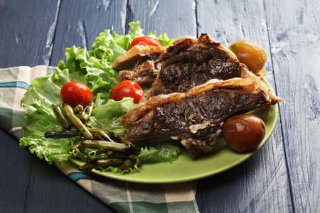 loin chops: Grilled lamb loin chops with pickled tomatoes on lettuce leaves over wooden tabletop Stock Photo