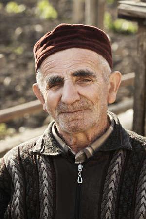grayness: Portrait of elderly caucasian man wearing cap sitting in his garden
