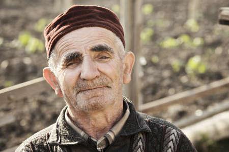 grayness: Portrait of senior caucasian man wearing cap sitting in his garden Stock Photo