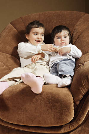 pleasant emotions: Two little brunnete funny caucasian sisters siting in chair