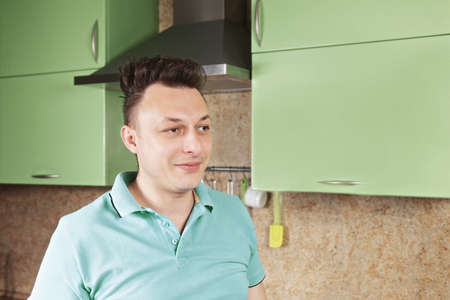 contented: Contented brunette caucasian guy standing at the kitchen looking sideways