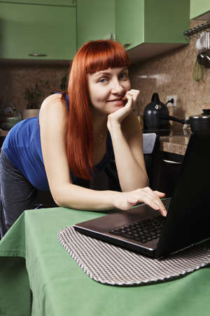 pleasant emotions: Positive redhead caucasian pregnant woman working on laptop at the kitchen
