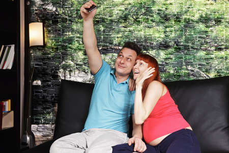 pleasant emotions: Pregnant caucasian couple taking selfie while sitting on a couch