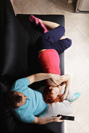 lays down: Pregnant couple watching TV she lays down on sofa while he sits with remote control overhead view