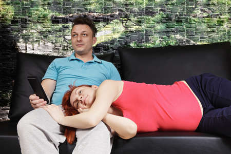 lays down: Pregnant couple watching TV she lays down on sofa while he sits with remote control