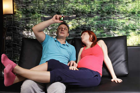 couple on couch: Guy examining medicine while pregnant couple sitting on the couch