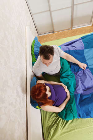 pleasant emotions: Pregnant caucasian couple chatting in bed overhead view