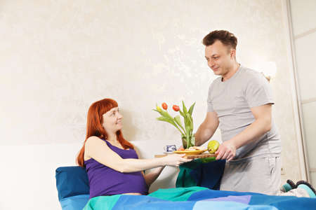 pleasant emotions: Guy serves breakfast for pregnant wife to bed Stock Photo