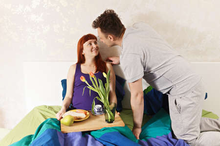 human relations: Pregnant woman enjoys breakfast in bed brought by husband