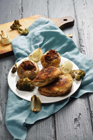 bleu: Cordon bleu cutlets and stuffed potatoes on a wooden tabletop Stock Photo