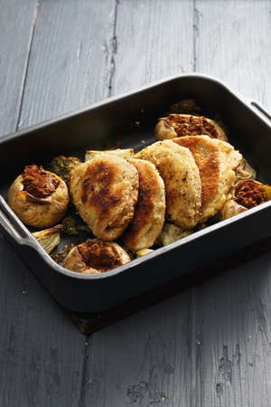 bleu: Oven tray with cordon bleu cutlets and stuffed vegetables on a wooden tabletop Stock Photo