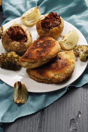 bleu: Cordon bleu cutlets and stuffed potatoes on a wooden tabletop closeup
