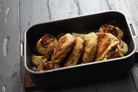 bleu: Tray with cordon bleu cutlets and stuffed potatoes on a wooden tabletop