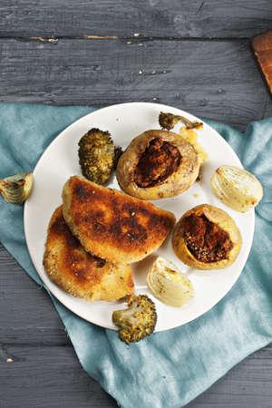 bleu: Cordon bleu cutlets and stuffed potatoes on a wooden tabletop overhead Stock Photo
