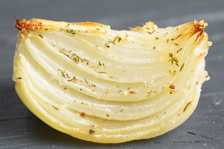 tabletop: Baked onion on a wooden gray tabletop closeup