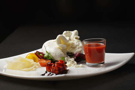 mediterranian: Plate of burrata cheese with strawberry gazpacho sauce and tomatoes in darkness