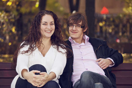 pleasant emotions: Positive young caucasian couple sitting on on the bench outdoors. Toned photo