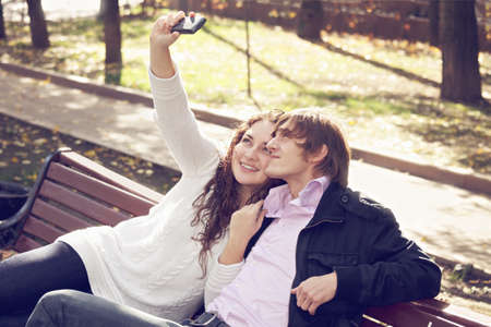 pleasant emotions: Caucasian couple taking selfie potographs while sitting on the bench in a park. Toned photo