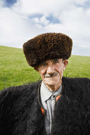 Elderly caucasian man in felt cloak and sheepskin fur hat which is traditional wear of Caucasus shepherds standing on a sunny meadow photo