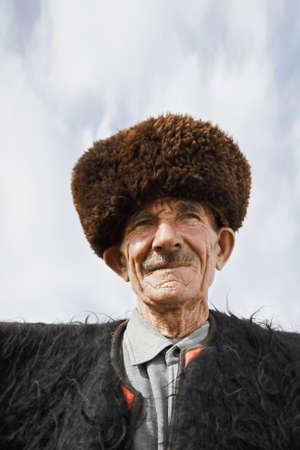 sheepskin: Aged caucasian man in felt cloak and sheepskin fur hat low angle view