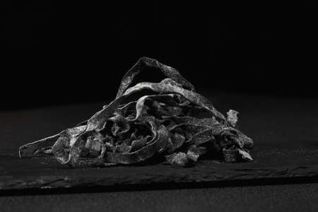 soaked: Black dried noodles soaked in a cuttlefish ink on a stone in darkness Stock Photo