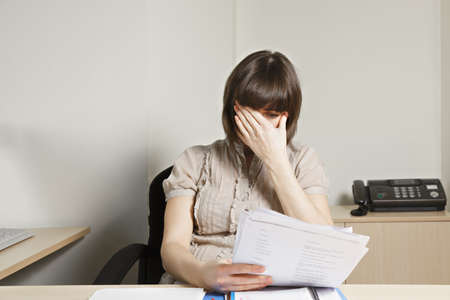 Stressed young caucasian brunette female office worker doing paperwork at desk photo