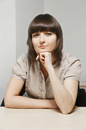 Young confident caucasian brunette female office worker sitting at desk photo