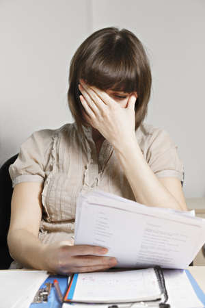 Stressed young caucasian brunette female clerk doing paperwork photo