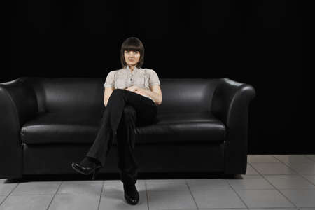 Serious young caucasian brunette female office worker sitting on couch photo