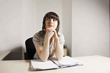Young caucasian brunette female office worker at paperwork looking sideways photo