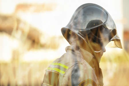 Rescuer in helmet and uniform profile view through flames firefighting concept Stock Photo