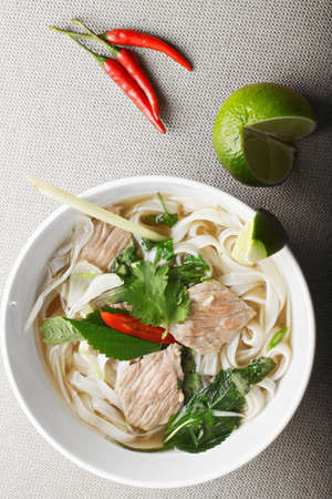 popular soup: Vietnamese traditional noodle pho bo soup made of  broth, herbs, meat and rice noodles. It is a popular street food in Vietnam being served at any time of the day, starting from breakfast. Overhead shot