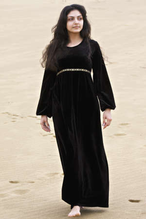 pleasant emotions: Pretty young caucasian brunette woman walking in desert Stock Photo