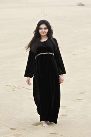 pleasant emotions: Pretty young caucasian brunette woman walking in sands