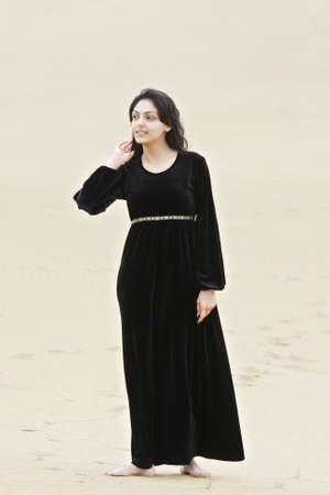 pleasant emotions: Young brunette caucasian woman in black dress standing in desert Stock Photo