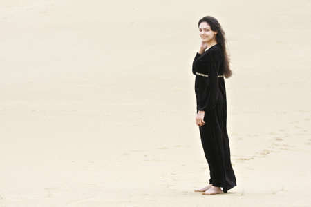 pleasant emotions: Young brunette caucasian woman in black dress standing on sand