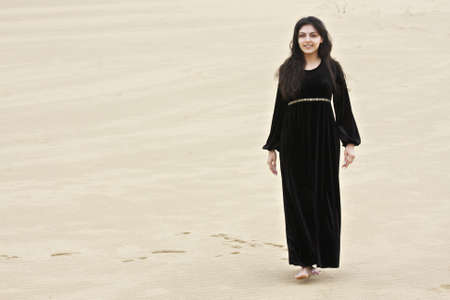 pleasant emotions: Positive young caucasian brunette woman walking in sands