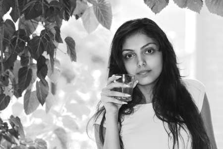 folliage: Portrait of young caucasian brunette woman with glass of drink. Black and white shot