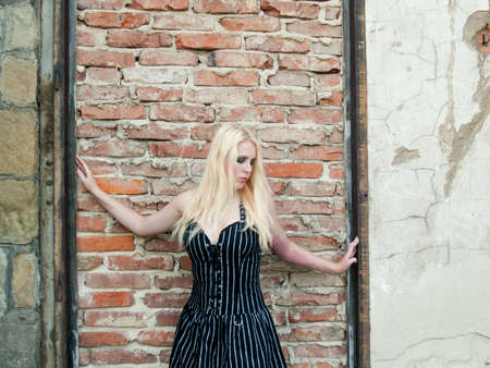 gothic girl in front of an old brick wall photo