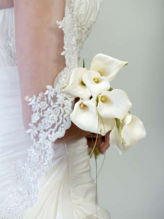 bridal bouquet made of calla flowers in bride´s hands photo
