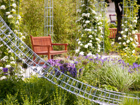 Garden with constructions for climbing plants, flowering roses and ornamental grasses
