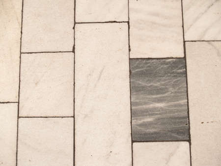 Detail of white paving with a dark paving brick