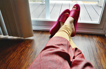 Bored housewife with plastic slippers on sitting on the floor in the apartment looking out of the balcony window during coronavirus lockdown 免版税图像 - 146200913